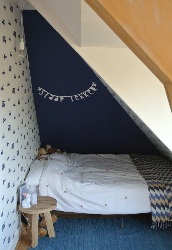Het slaapplekje is een lekker knus holletje geworden door het behang in de nis en de donker blauwe kleur.